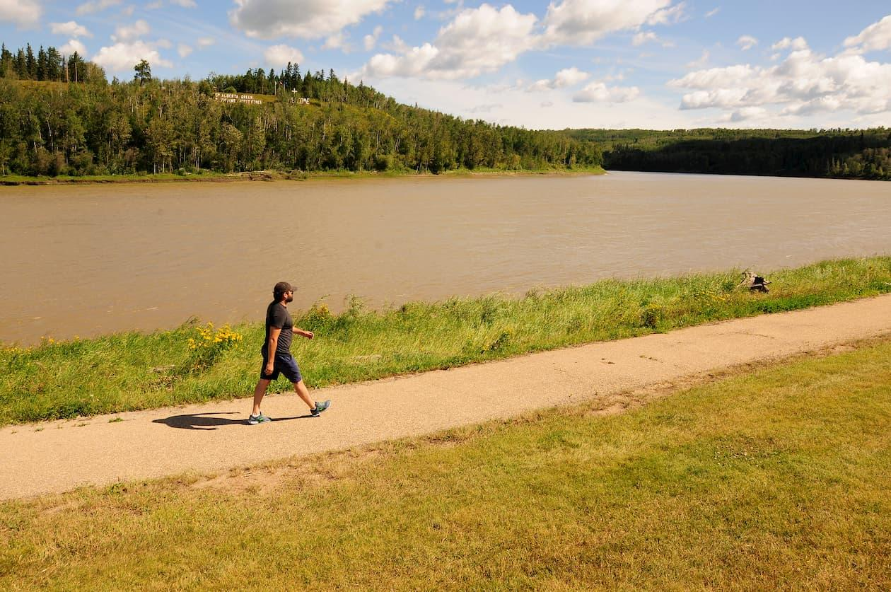 A man walks along the river path in Athabasca