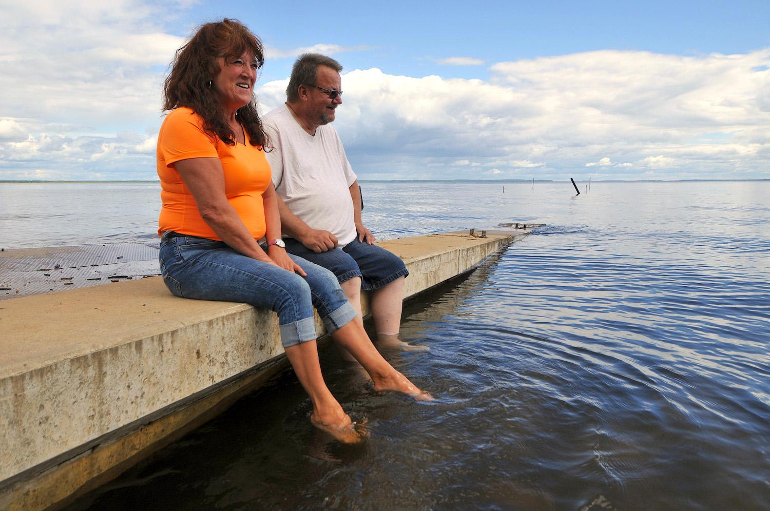 A couple sit on a dock in Plamondon Lac La Biche looking out at the water