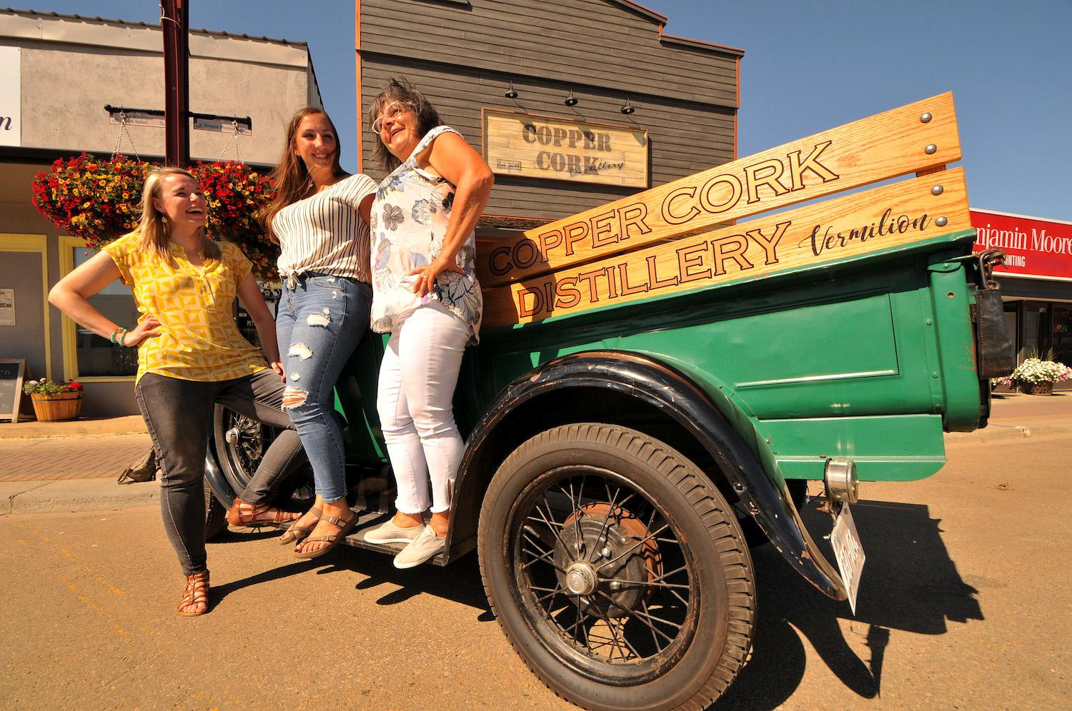 Three women stand in front of a 1928 Model A Ford Roadster Truck outside Copper Cork Distillery
