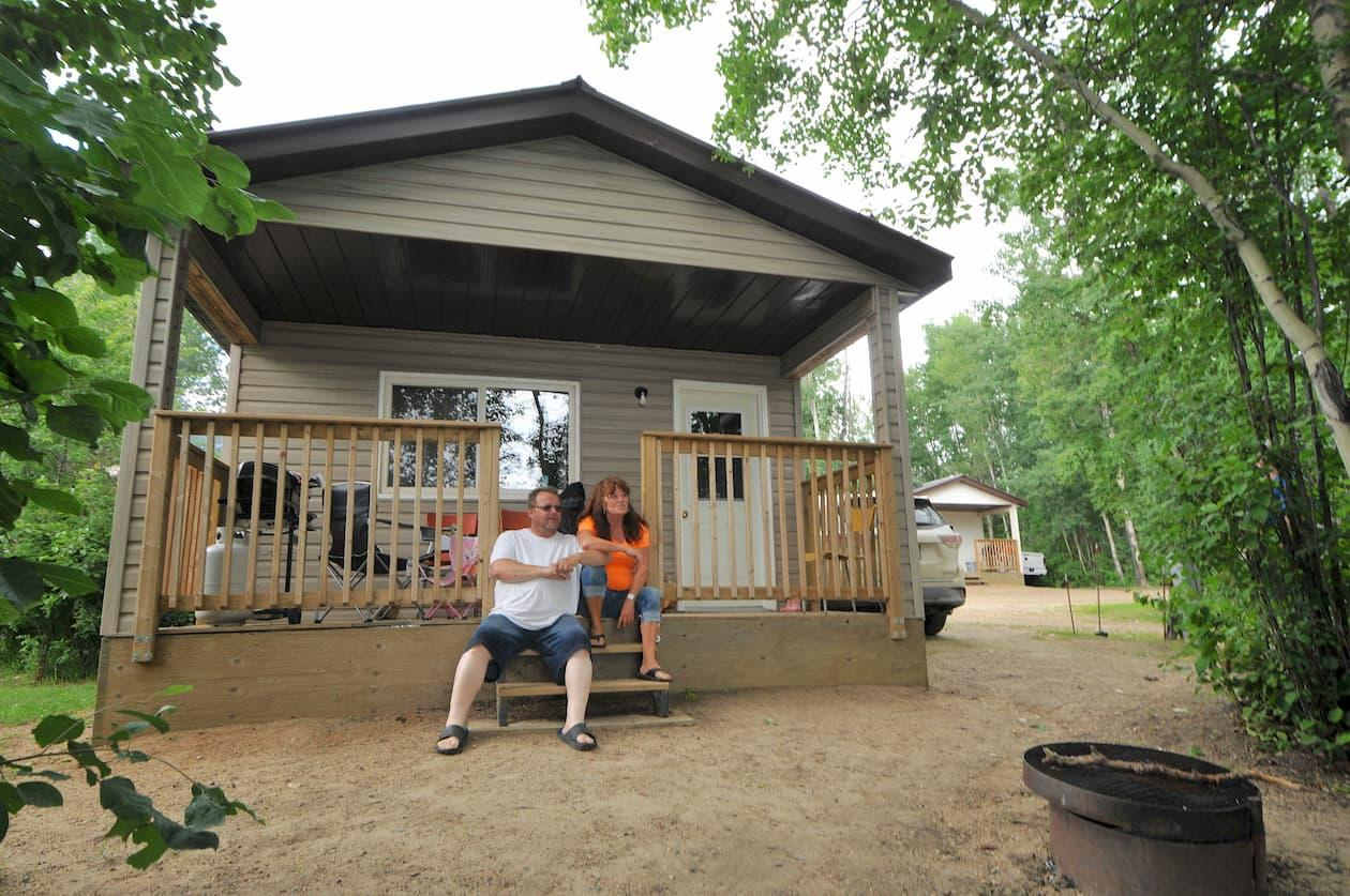 A couple relaxes on the steps of a house in Plamondon Lac La Biche