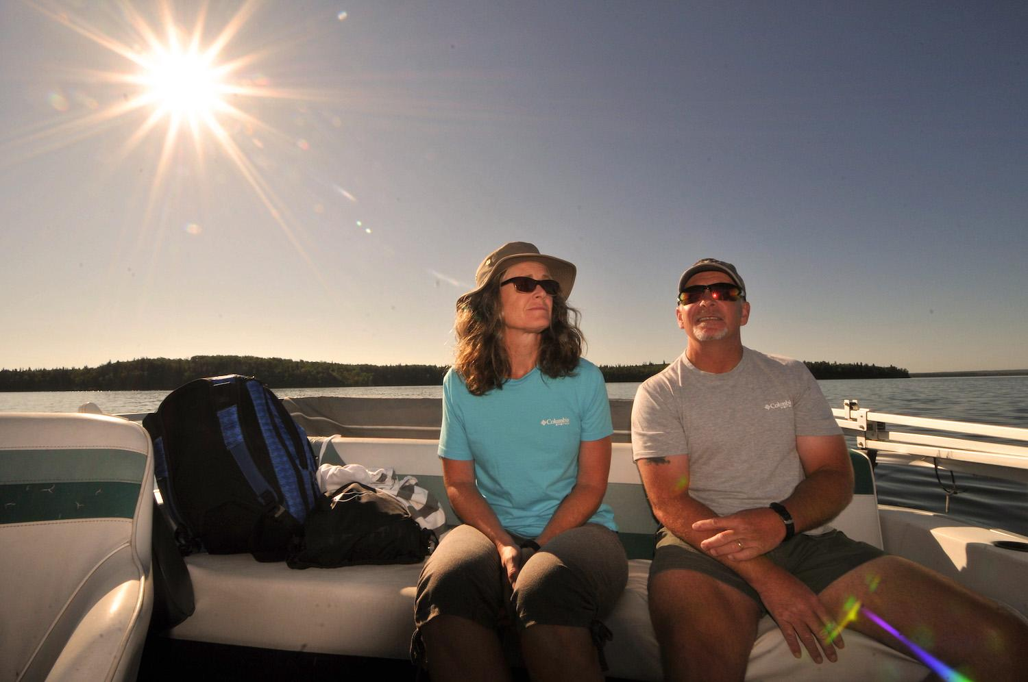 A couple in the sun on a boat in Cold Lake